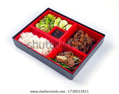 Japanese Bento Box with pork stew with pepper, stir fried beef, salad and cucumber. Bento box isolated on white background