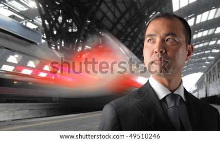 Japanese Businessman standing on the platform of a train station