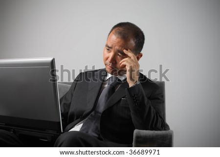 japanese businessman with sad expression working with laptop