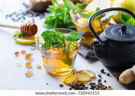 Japanese chinese tea teapot lemon ginger honey mint on a white table. Warm drink beverage infusion in glass for cold flu winter fall days ストックフォト ©