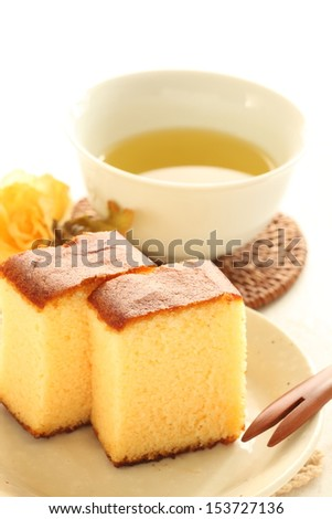 Japanese confection, Nagasaki cake Kasutera and green tea with flower on background