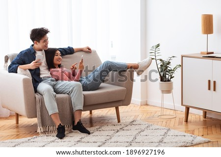 Japanese Couple Using Cellphones Texting And Browsing Internet Relaxing Sitting On Couch Indoor. Weekend Leisure. Happy And Relaxed Asian Family Using Mobile Application Resting At Home