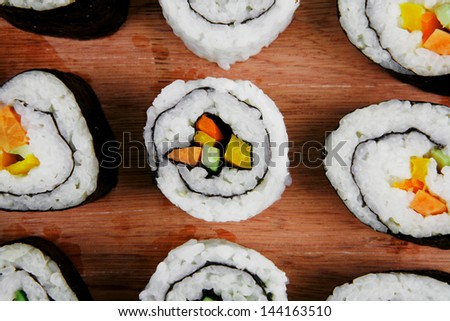 Japanese Cuisine - Maki Roll with Deep Fried Vegetables inside . on wooden plate . isolated over white background