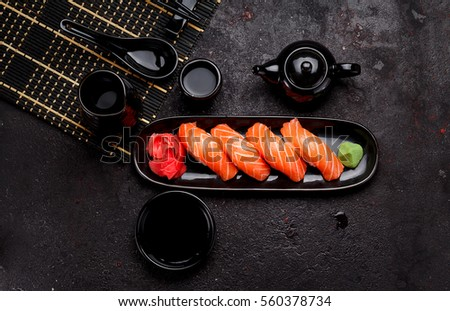 Japanese cuisine. Salmon sushi (nigiri) on a black plate and dark concrete background. #560378734