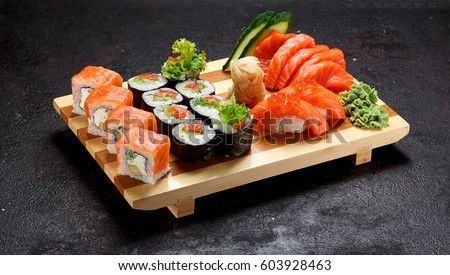 Japanese cuisine. Sushi set on a wooden plate over dark stone background.