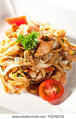 Japanese Cuisine - Udon (thick wheat noodles) with Salmon and Vegetables. Garnished with Cherry Tomato