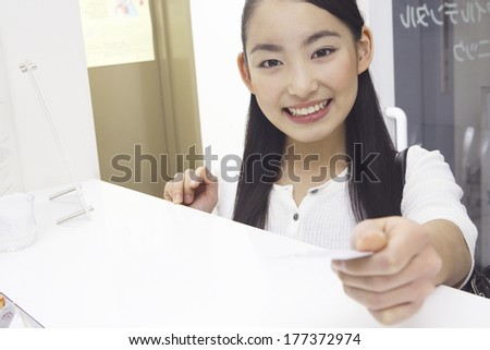 Japanese dental patient submitting patient registration card at the dentist