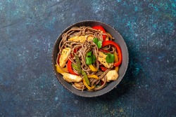 Japanese dish buckwheat soba noodles with chicken and vegetables carrot, bell pepper and green beans in grey bowl, top view, copy space.