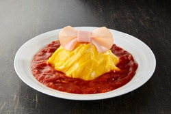 Japanese Dressed Omu-Rice (Omelette Rice) with a ribbon made of roast ham on top.  Omu-Rice is One of Japan's most popular dishes.Typically, ketchup rice is wrapped in omelette.