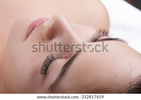 Japanese eyelash extensions. Long eyelashes. Beautiful dark-haired girl lies on a couch in the office of the master eyelash. View from the forehead .