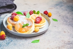Japanese fluffy pancakes with raspberries in a gray plate, gray background. Japanese cuisine concept.