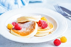 Japanese fluffy pancakes with raspberries in a white plate, white background. Japanese cuisine concept.