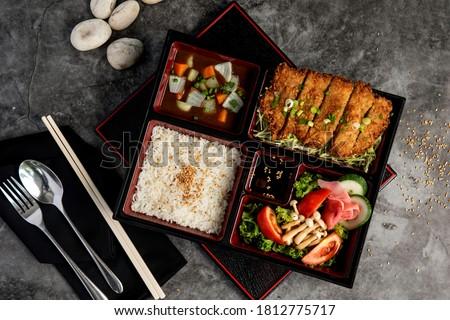 Japanese food bento set with tonkatsu and tempura on dark stone background