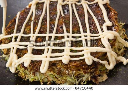 Japanese food cooking Okonomiyaki,Squeezing mayonnaise on a Japanese pizza.