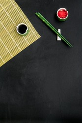 Japanese food cooking set with soy sauce, ginger, bamboo sticks for sushi on black background top view copy space