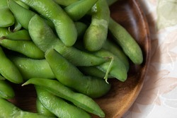 Japanese food edamame nibbles, boiled green soy beans Close up