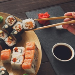 Japanese food restaurant, maki plate, platter set. Hand takes roll. Set with chopsticks, ginger, soy sauce at rustic wood background and black stone. POV at black. Instagram style.