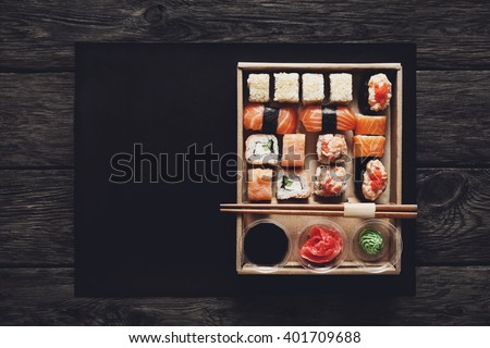 Japanese food restaurant, sushi maki gunkan roll plate or platter set. ?opy space, chopsticks, ginger, soy sauce, wasabi. Sushi at rustic wood background in take away, delivery box. Top view.