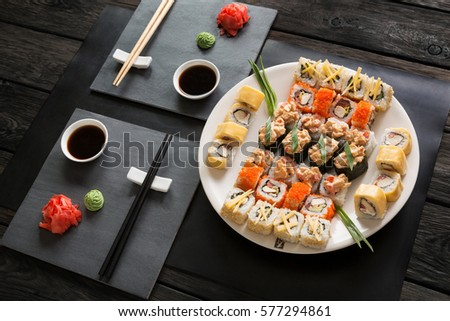 Japanese food restaurant, sushi maki gunkan roll platter. Set for two with chopsticks, ginger, soy, wasabi. Above view on rustic wood background and black slate plates. #577294861