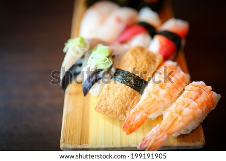 Japanese foods include sushi, nigiri, sashimi, served on small plate on a wooden background