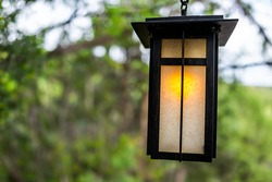 Japanese garden closeup of yellow illuminated hanging lantern in traditional style with blurry bokeh background of green trees in park at evening