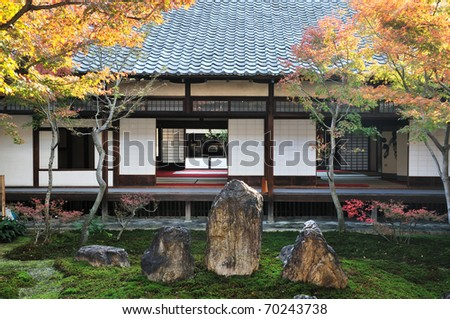 Japanese garden seen through a traditional sliding wall of a wooden house.