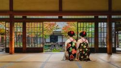 Japanese Geisha Look at a Small Rock Garden at  Kennin-ji Temple in Colorful Autumn