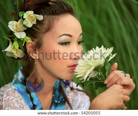 Japanese girl holds flower, against green grass