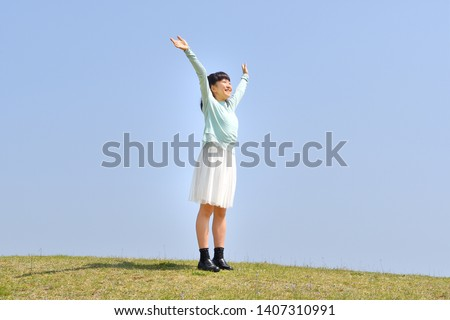 Japanese girl stretching in the blue sky