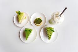 Japanese green tea cake topping, crepe cake, cheese cake dessert with green tea powder over the cake on white plate. matcha green tea milk frappe.