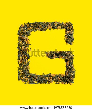 Japanese green tea Genmaicha. G-shaped fried brown rice tea leaves on bright yellow background with shadow. Slimming trend tea concept. Natural product. Self-care and health Photo stock ©