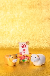 Japanese greeting Card with handwriting ideograms Geishun meaning Welcoming Spring and two cute Zodiacal animals figurines of cow for the Year of the Ox on a golden background.