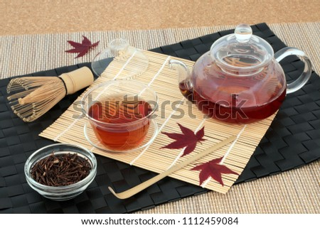 Japanese kuchika roasted twig green tea with glass teapot & cup, dried twigs in a bowl, stirrer, whisk & maple leaves on bamboo background. Has many health benefits including rejuvenating properties. #1112459084