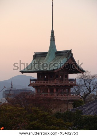 Japanese landscape of pagoda and hills at dusk in Kyoto, Japan, a traditional Japanese building or temple  with a green roof and carved wood balconies