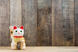 Japanese lucky cat on wooden