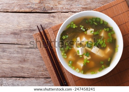 Japanese miso soup in a white bowl on the table. horizontal view from above