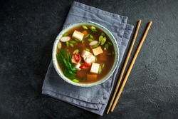 Japanese miso soup in ceramic bowl on black stone table, copy space. Asian miso soup with tofu.