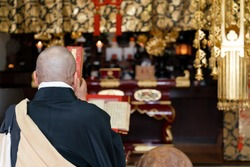 Japanese monk praying at a temple
