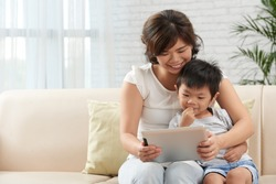 Japanese mother and son watching something on tablet screen together