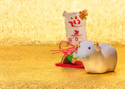 Japanese New Year Card with handwriting ideograms Geishun meaning Welcoming Spring on a washi paper decoration and a cute Zodiac animal figurine of a cow for the 2021 Year of the Ox on a golden paper