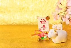 Japanese New Year's Card with the ideograms Geishun or Welcoming Spring with a cute hand painted Zodiacal animal figurine of cow for the 2021 Year of the Ox on a cherry blossoms and golden background.