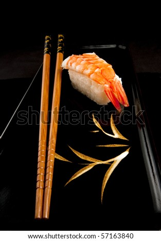 Japanese nigiri sushi with rice and prawn and chopsticks on a black Japanese plate.