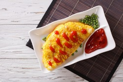 Japanese Omurice omelet stuffed with rice and chicken on a plate. horizontal top view