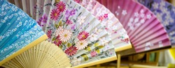 Japanese paper fans. Several folding fans  with floral patterns displayed in a souvenir shop in Tokyo, Japan.
