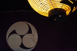 Japanese paper lantern lit and a fabric screen with emblem on background