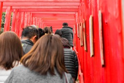 Japanese people doing Hatsumode or Shrine visitations during new year. People are walking through red torii gates leading to a shrine to pray.