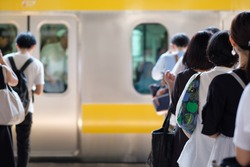 Japanese people queuing for boarding a train in Tokyo.