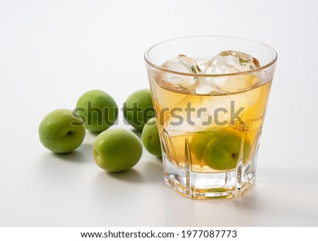 Japanese plum wine and unripe plums on a white background.