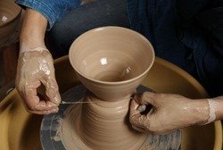 Japanese pottery master technique/Cutting the bowl/A Japanese pottery master cutting a finished bowl from the clay on his pottery wheel