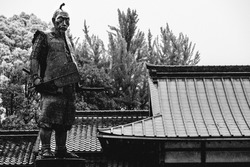 Japanese roofs and samurai sculpture under the rain in black and white